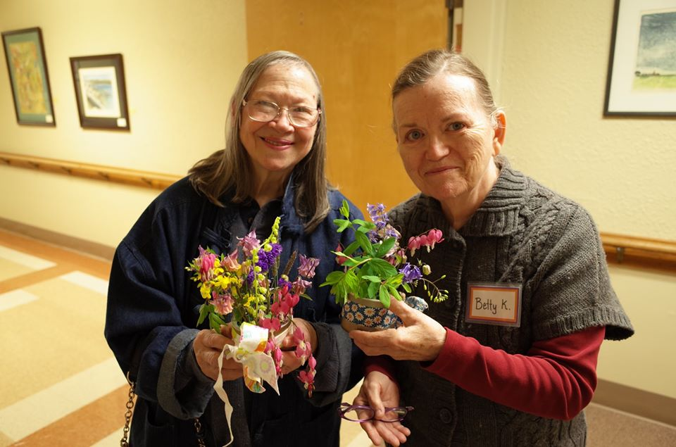 Two Grace Center participants showing off their bouquets they made in a flower arranging activity