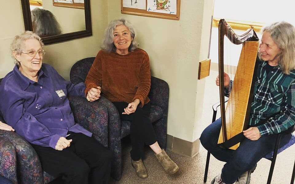 A Grace Center volunteer playing a miniature harp for participants