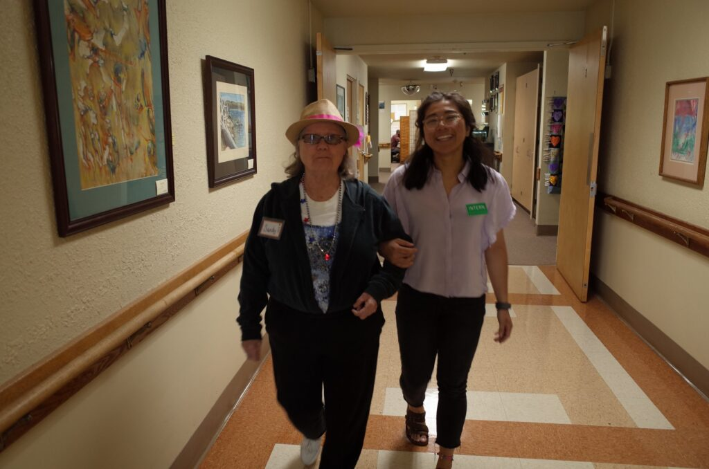 A Grace Center intern walking arm in arm with a participant